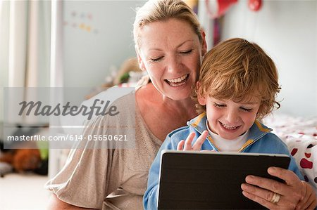 Mother using a digital tablet with her son Stock Photo - Premium Royalty-Free, Image code: 614-05650621