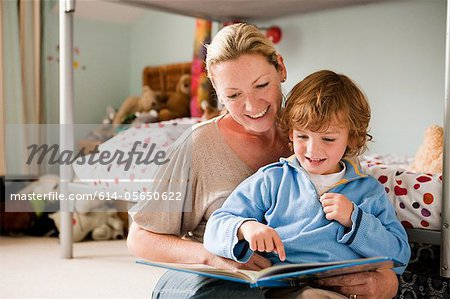 Mother reading a book with her son in his bedroom Stock Photo - Premium Royalty-Free, Image code: 614-05650622