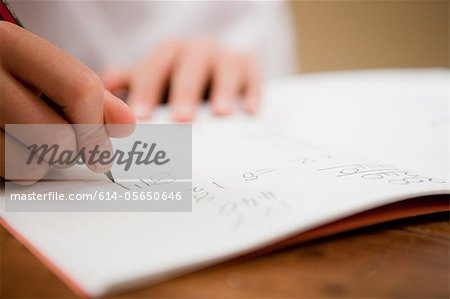 Close up of the hands of a young boy writing in a textbook Stock Photo - Premium Royalty-Free, Image code: 614-05650646