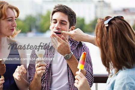 Friends eating icecreams and lollypops Stock Photo - Premium Royalty-Free, Image code: 614-05650689