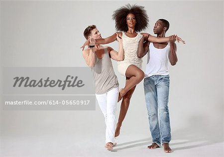 Two men holding a young woman off the ground Stock Photo - Premium Royalty-Free, Image code: 614-05650917