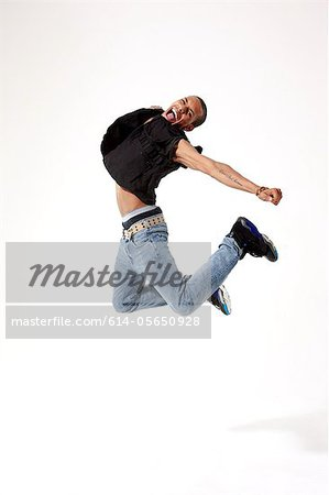 Jubilant young man in mid air Stock Photo - Premium Royalty-Free, Image code: 614-05650928