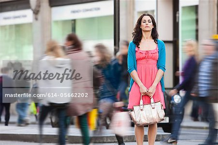 Mid adult woman in pink dress standing still in crowded city Stock Photo - Premium Royalty-Free, Image code: 614-05662202