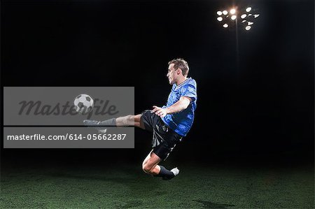 Young soccer player leaping into air to kick ball Stock Photo - Premium Royalty-Free, Image code: 614-05662287