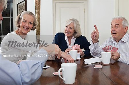 Senior friends playing cards Stock Photo - Premium Royalty-Free, Image code: 614-05792349