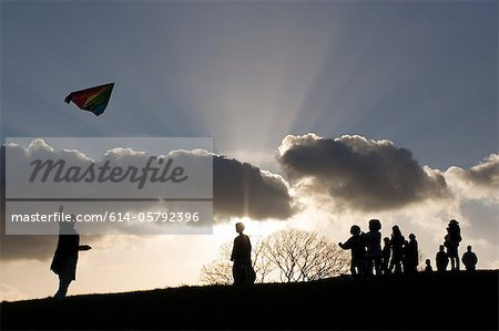Silhouetted people in park with kite Stock Photo - Premium Royalty-Free, Image code: 614-05792396