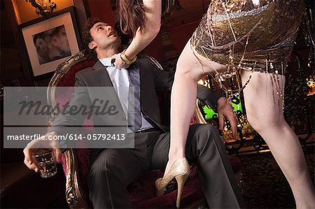 Woman grabbing businessman in bar Stock Photo - Premium Royalty-Free, Image code: 614-05792413