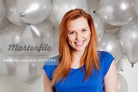 Happy young woman in front of balloons Stock Photo - Premium Royalty-Free, Image code: 614-05792504