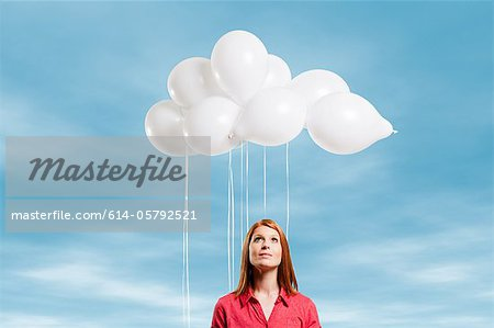 Young woman looking at thought bubble made of balloons Stock Photo - Premium Royalty-Free, Image code: 614-05792521