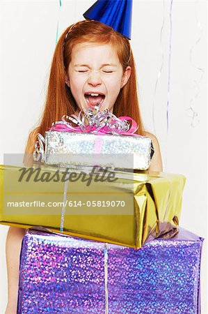 Screaming girl with stack of birthday gifts Stock Photo - Premium Royalty-Free, Image code: 614-05819070