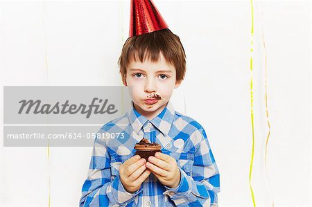 Boy with cupcake around his mouth Stock Photo - Premium Royalty-Free, Image code: 614-05819073