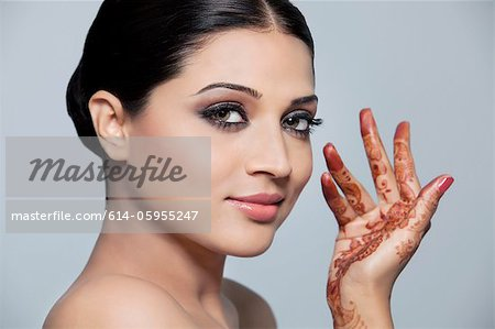 Portrait of a beautiful woman with mehndi Stock Photo - Premium Royalty-Free, Image code: 614-05955247