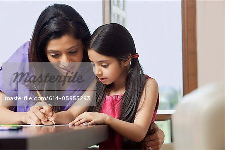 Mother teaching her daughter to write Stock Photo - Premium Royalty-Free, Image code: 614-05955293