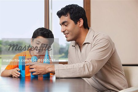 Father and son playing with building blocks Stock Photo - Premium Royalty-Free, Image code: 614-05955297