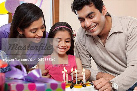 Girl celebrating her birthday with parents Stock Photo - Premium Royalty-Free, Image code: 614-05955300