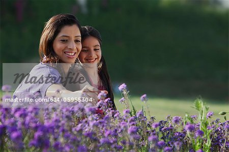 Mother and daughter plucking flowers
