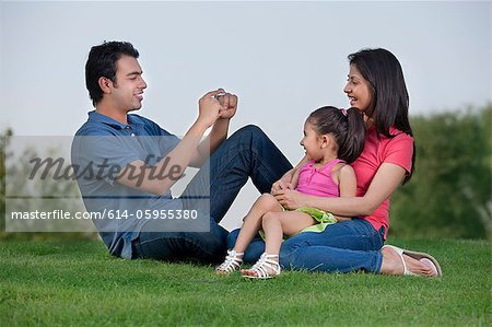 Man taking a photograph of his family Stock Photo - Premium Royalty-Free, Image code: 614-05955380
