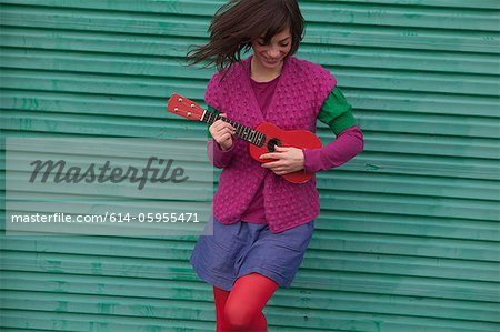 Young woman playing ukulele Stock Photo - Premium Royalty-Free, Image code: 614-05955471