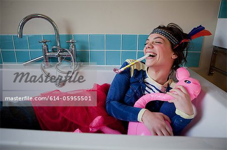 Young woman in bath, wearing costume and blowing party blower Stock Photo - Premium Royalty-Free, Image code: 614-05955501