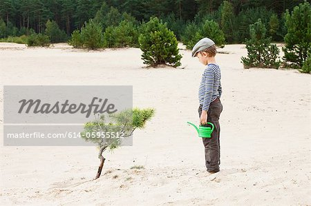 Boy with watering can, looking at plant in sand Stock Photo - Premium Royalty-Free, Image code: 614-05955512