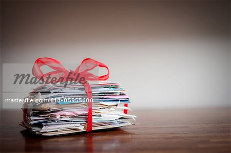 Stack of letters tied together with ribbon Stock Photo - Premium Royalty-Free, Image code: 614-05955600