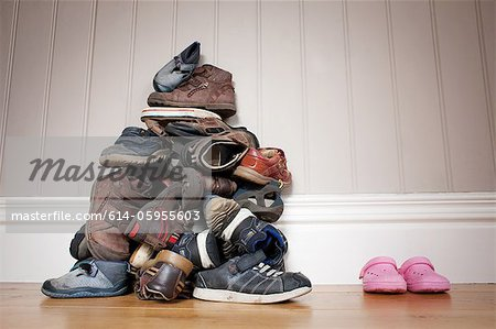 Large pile of boy's shoes beside one pair of girl's shoes Stock Photo - Premium Royalty-Free, Image code: 614-05955603