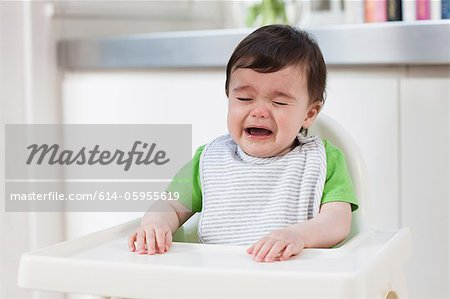 Baby boy in high chair, crying Stock Photo - Premium Royalty-Free, Image code: 614-05955619