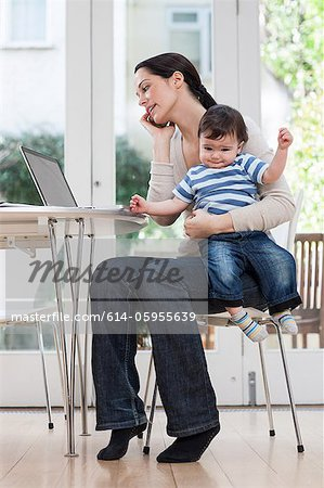 Mother holding baby boy, using cellphone and laptop Stock Photo - Premium Royalty-Free, Image code: 614-05955639