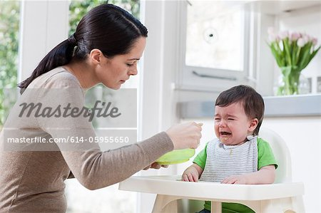 Mother feeding crying baby son Stock Photo - Premium Royalty-Free, Image code: 614-05955650