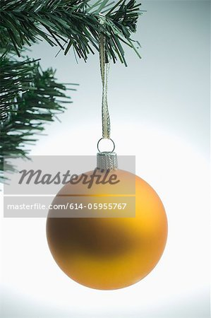 Yellow christmas bauble hanging on tree Stock Photo - Premium Royalty-Free, Image code: 614-05955767