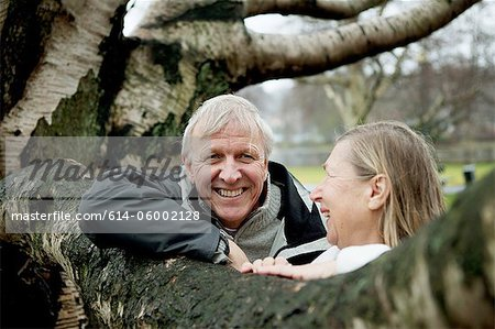 Senior couple leaning against tree, smiling Stock Photo - Premium Royalty-Free, Image code: 614-06002128