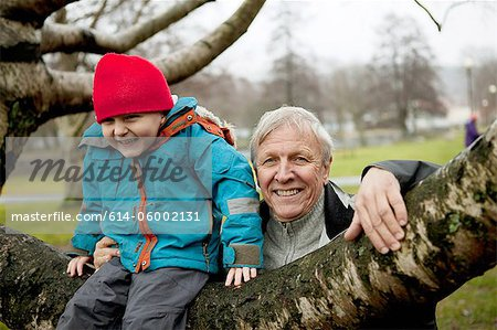 Granfather and boy sitting on tree branch, smiling Stock Photo - Premium Royalty-Free, Image code: 614-06002131