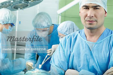 Surgeon looking at camera, colleagues in background performing operation Stock Photo - Premium Royalty-Free, Image code: 614-06002158