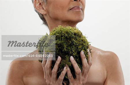 Senior woman holding plant, studio shot Stock Photo - Premium Royalty-Free, Image code: 614-06002253