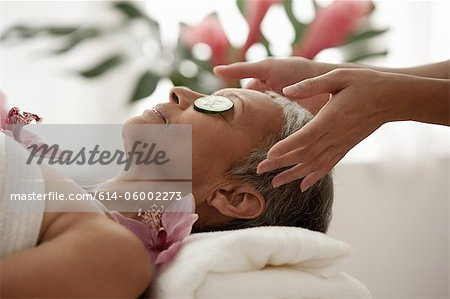 Senior woman wearing cucumber slices and relaxing on massage table Stock Photo - Premium Royalty-Free, Image code: 614-06002273