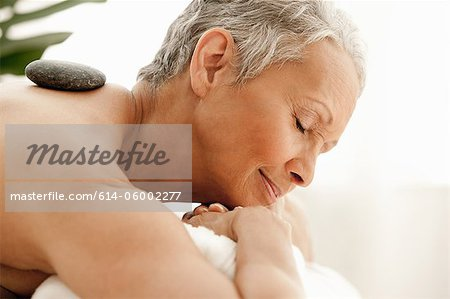 Senior woman receiving stone therapy Stock Photo - Premium Royalty-Free, Image code: 614-06002277
