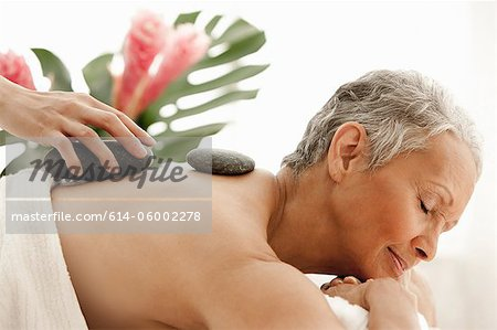 Senior woman receiving stone therapy Stock Photo - Premium Royalty-Free, Image code: 614-06002278