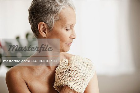 Senior woman exfoliating with mitt Stock Photo - Premium Royalty-Free, Image code: 614-06002303