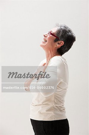 Side view of mature woman smiling, studio shot Stock Photo - Premium Royalty-Free, Image code: 614-06002376