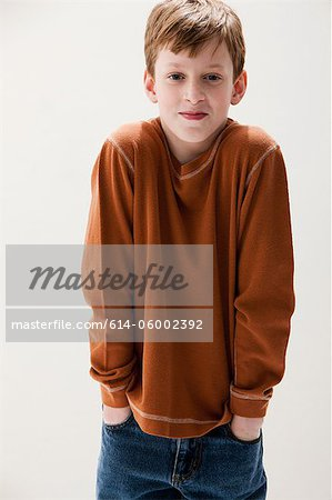 Boy in brown sweater with hands in pockets, studio shot Stock Photo - Premium Royalty-Free, Image code: 614-06002392