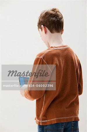 Boy in brown sweater playing hand held video game, studio shot Stock Photo - Premium Royalty-Free, Image code: 614-06002396