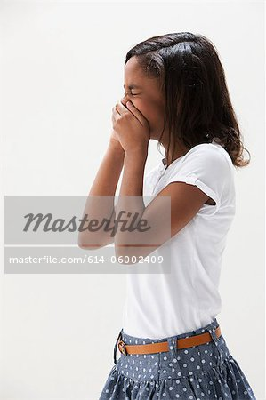 African American girl laughing, studio shot Stock Photo - Premium Royalty-Free, Image code: 614-06002409
