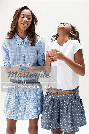 African American sisters laughing together, studio shot Stock Photo - Premium Royalty-Free, Image code: 614-06002415