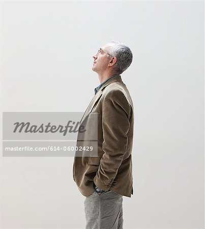 Mature man with hands in pocket looking up, studio shot Stock Photo - Premium Royalty-Free, Image code: 614-06002429