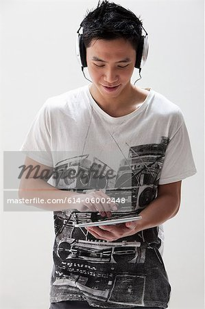 Young Asian man using digital tablet with headphones, studio shot