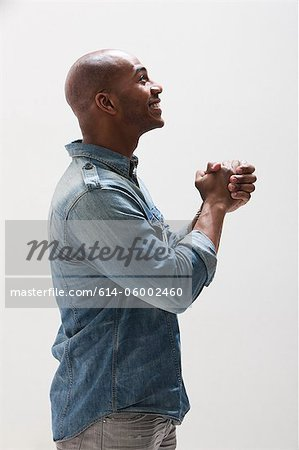 African American man with hands clasped, studio shot Stock Photo - Premium Royalty-Free, Image code: 614-06002460