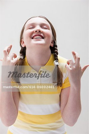 Girl with fingers crossed, studio shot Stock Photo - Premium Royalty-Free, Image code: 614-06002461