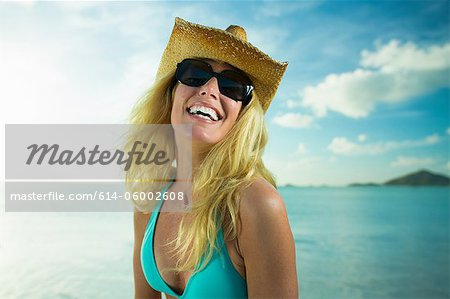 Happy woman in sunglasses and cowboy hat by the ocean Stock Photo - Premium Royalty-Free, Image code: 614-06002608