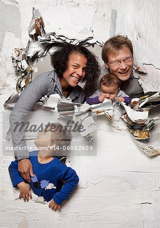 Happy family busting through a wall Stock Photo - Premium Royalty-Free, Image code: 614-06002609