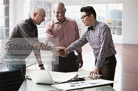 Businessmen shaking hands in office Stock Photo - Premium Royalty-Free, Image code: 614-06043786